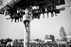 ©Ahmed Ano. Des civils escaladent d'énormes panneaux publicitaires pour crier « Liberté, paix et justice ». Sit-in, quartier général militaire, Khartoum, 19 avril 2019.