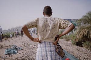 ©Muhammad Salah. Un manifestant dont l'inscription au dos de sa chemise signifie « Un révolutionnaire de Kalakla, que la dictature tombe ! » ; il se tient sur la ligne ferroviaire centrale de Khartoum qui faisait partie de la zone de sit-in du QG de l'armée. Khartoum, Soudan, 13 avril 2019.